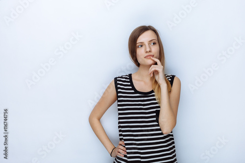 Fotografering  Portrait of happy young beautiful woman in striped shirt touching her lips posin