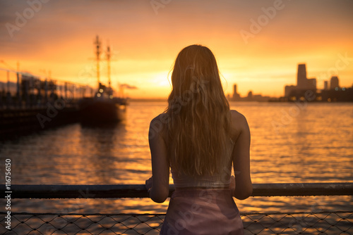 Keuken foto achterwand Ontspanning Beautiful girl standing on ocean pier with yacht and looking at sunset sky. Girl from the back outdoors near the ocean.