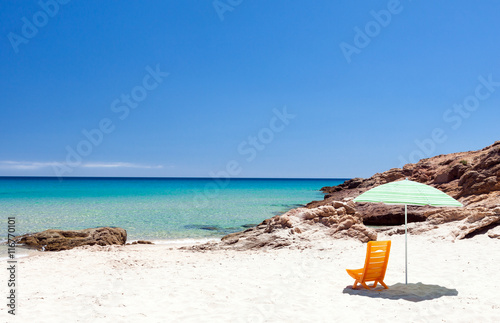 Photo  Lonely lounge chair with sun umbrella on a beach in Sardinia, Italy