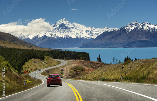 Poster Oceanië Red car on the road to Mt.Cook,New Zealand