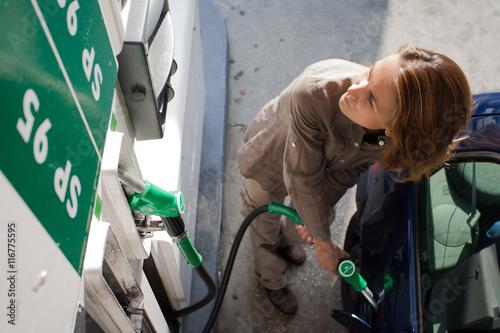 Fotografie, Obraz  femme dans le doute à une pompe à essence