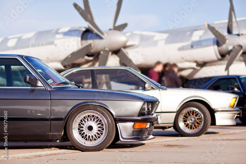 Photo  Right front side of two old european sport cars with plane on background