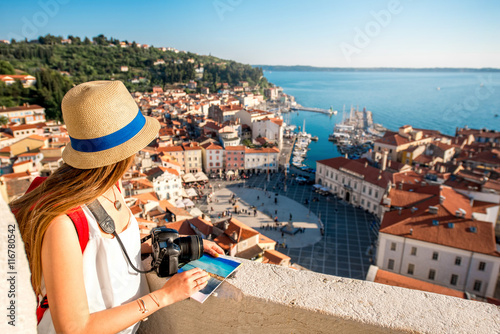 Valokuva Young female traveler with red backpack and hat enjoying the view from George's tower on Piran old town