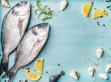 Fresh Raw Sea Bream Fish Decorated With Lemon Slices, Herbs And Sea Shells On Blue Wooden Background. Healthy Food Concept, Top View, Copy Space
