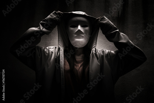 Fotografía  A stranger woman wearing hoodie with white mask hiding in the dark,Scary backgro