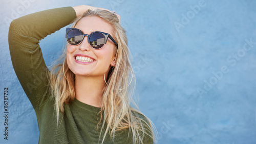 Stylish young woman in sunglasses smiling Fototapete