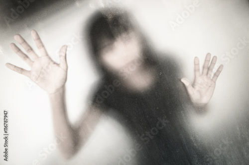 Fotografía  No panic,woman behind stained or dirty window glass,Scary background for book co