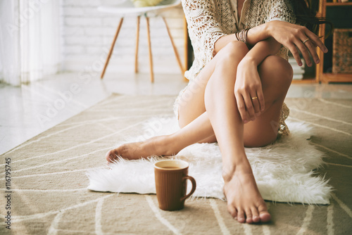 Valokuva Legs of woman sitting on the floor with cup of coffee