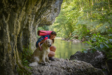 Female Hiker With Backpack And A Golden Retriever Staying On A Rock Close To A River