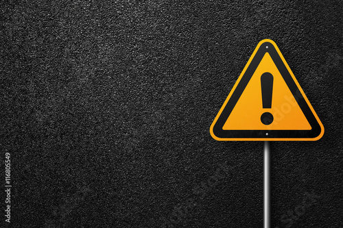 Fotografia  Road sign triangular shape with exclamation mark on a background of asphalt