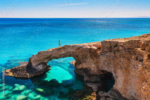 In de dag Cyprus Woman on the beautiful natural rock arch near of Ayia Napa, Cavo Greco and Protaras on Cyprus island, Mediterranean Sea. Legendary bridge lovers. Amazing blue green sea and sunny day.