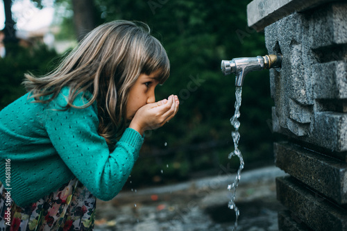 Fotografía  girl drinking water from a fountain