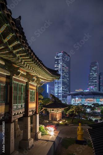 Naklejka premium Ornate building at the Bongeunsa Temple and view of Gangnam in Seoul, South Korea at night.