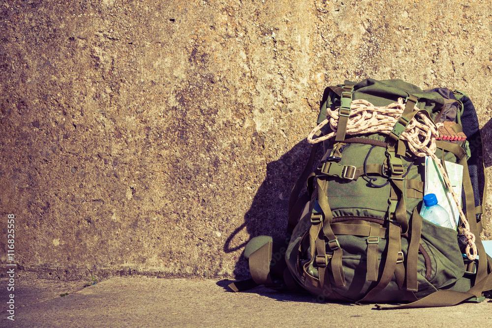 Fototapeta Hiking backpack camping equipment outdoor on grunge wall