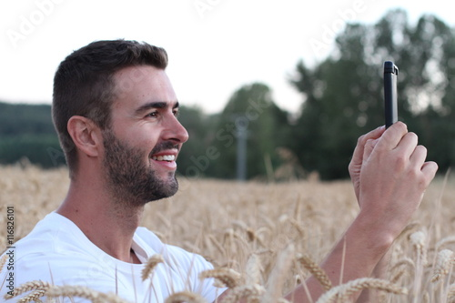 Young smiley man playing a video game in remote wheat field Poster