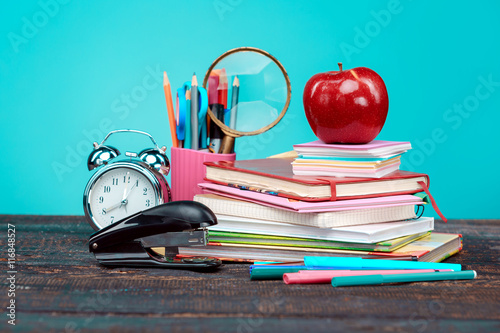 Stampe Back to School concept. Books, colored pencils and clock