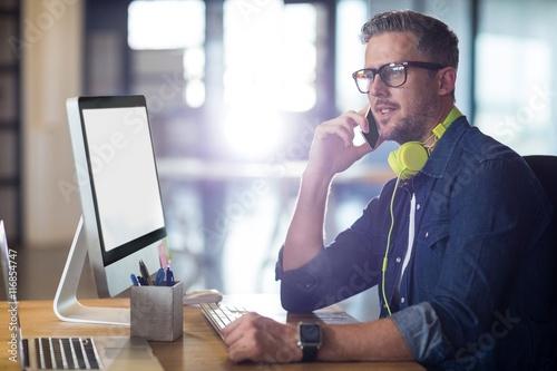Fotografie, Obraz  Man talking on phone in office
