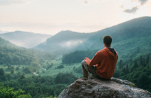 Traveler Young Man Sitting On Stone In The Summer Mountains And Enjoying View Of Nature