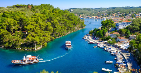 Paxos island panorama with boat entering the grand canal