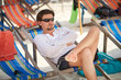 Young man in sunglasses and white clothes relaxing at the beach on a comfortable chair and staring thoughtfully into the distance