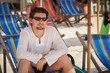 Young man in sunglasses and white clothes relaxing at the beach on a comfortable chair and looking into the camera