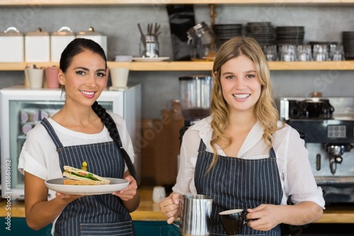 Fotografía  Portrait of two waitresses holding plate of meal and coffee jug