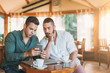 Two man at cafe using mobile phone