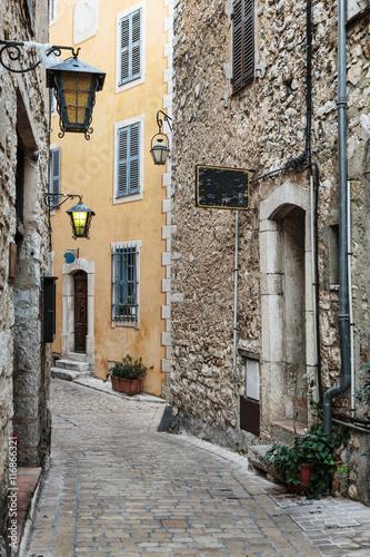 waska-brukowana-ulica-z-kwiatami-w-starej-wiosce-tourrettes