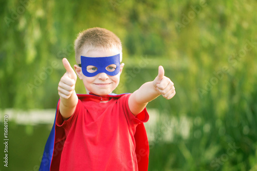 Photo  Kid in superhero costume showing thumbs up. T