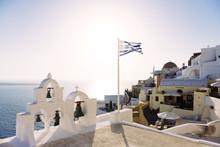Greece, Santorini, Oia, Greek Flag Waving On A Church At Sunset