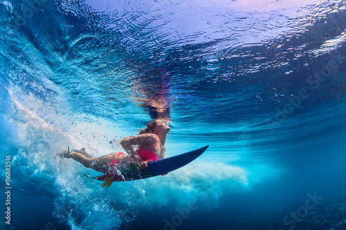 Foto  Young active girl wearing bikini in action - surfer with surf board dive underwater under big ocean wave
