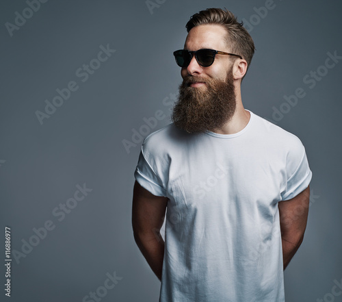 Stampa su Tela Bearded handsome man with sunglasses looking over