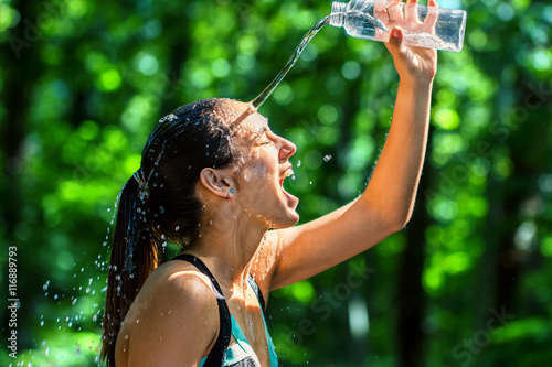 Photo  Girl pouring water on face after workout.
