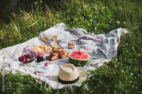 Photo sur Toile Pique-nique summer picnic on the rug. Fruits, berries, pastries and cheese