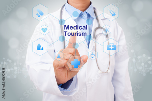 Fotografia  Doctor hand touching medical tourism sign on virtual screen