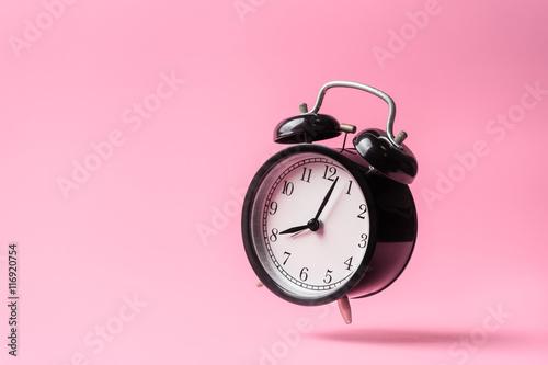 black vintage alarm clock falling on the floor with color backgr