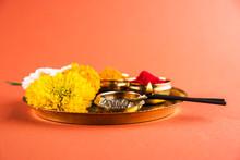 Beautifully Decorated Pooja Thali For Diwali Celebration To Worship, Huldi Or Turmeric Powder And Kumkum, Flowers, Scented Sticks In Brass Plate On Orange Background, Hindu Puja Thali