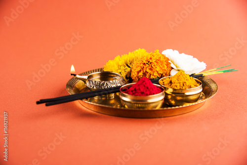 Beautifully Decorated Pooja Thali for diwali celebration to worship, huldi or turmeric powder and kumkum, flowers, scented sticks in brass plate on orange background, hindu puja thali