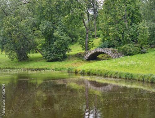 Poster Nature Каменный мостик у пруда в пригородном парке летом.