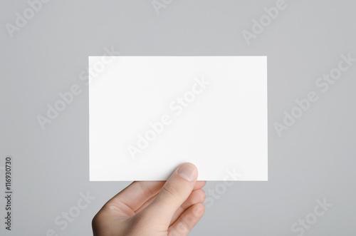 Fotografía  A6 Flyer / Postcard / Invitation Mock-Up - Male hands holding a blank flyer on a gray background