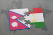 puzzle with the national flag of nepal and tajikistan on a world map background.