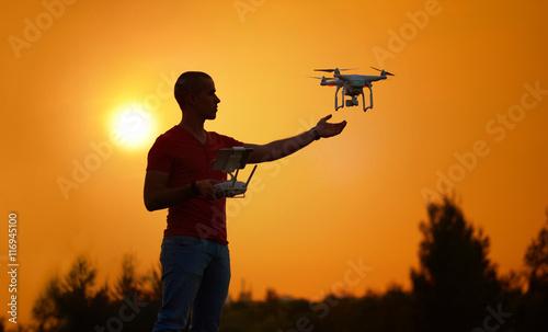 Deurstickers Militair Man controls a quadrocopter. Warm sunset photo