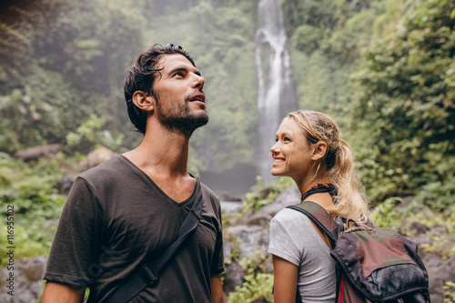 Young couple with backpack hiking in nature