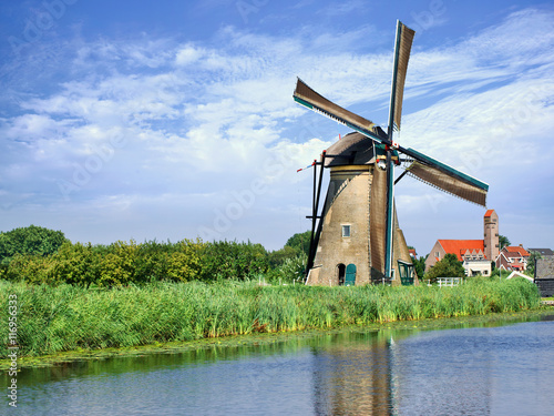 In de dag Molens Ancient wind mill reflected in blue canal on a summer day, Kinderdijk, The Netherlands.