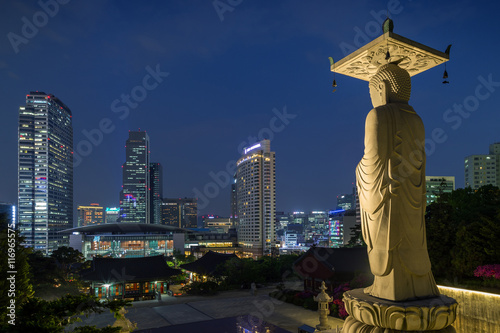 In de dag Seoel Mireuk Daebul statue (The Great Statue of Maitreya Buddha) at the Bongeunsa Temple and view of Gangnam in Seoul, South Korea at night.