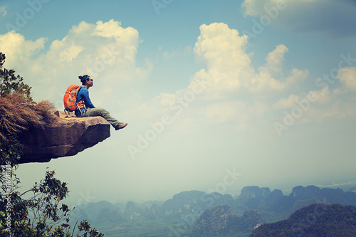 successful woman backpacker sit on mountain peak cliff Wallpaper Mural