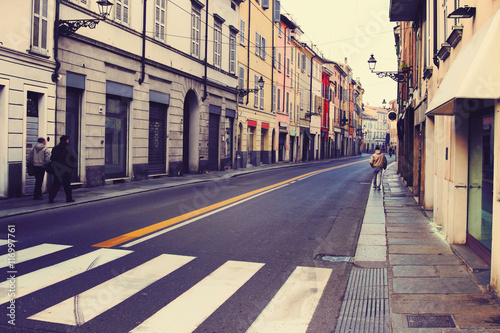 Old streets in historical center of Italian town, Parma, Italy. Narrow street and old pavement. Color toning effect applied.
