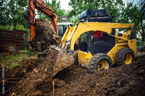 Fotografie, Obraz  Landscaping works with bulldozer and excavator at home construction site