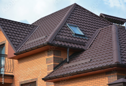 Fotografia New roofing construction with attic skylights, rain gutter system, roof windows and roof protection from snow board, snow guard exterior