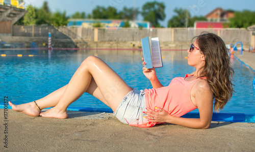 Valokuva  Girl reading a book by the pool.